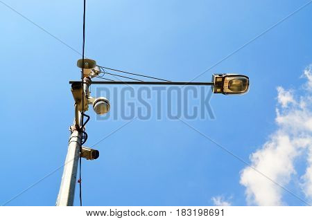 Loudspeaker and CCTV camera on lamp post against blue sky