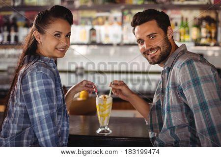 Portrait of happy couple having milkshake at counter in restaurant
