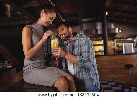Happy couple having milkshake in restaurant