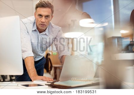 Portrait of businessman working on laptop while leaning at desk in office