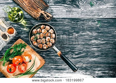 Fried meatballs on frying pan on black and white wood background with fresh tomatoes, oil and spices