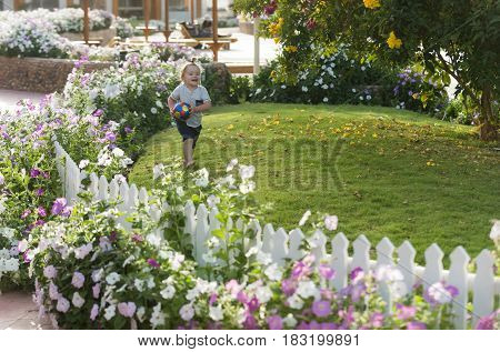 healthy lifestyle sport. Happy cute baby boy small child with long blond hair barefoot playing with colorful ball on green grass in garden with flowers on sunny summer on natural background
