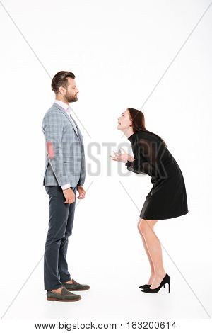 Image of offended young loving couple swear isolated over white background. Looking aside.