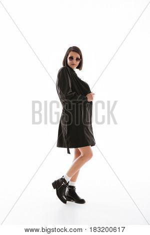 Image of pretty young lady wearing sunglasses standing isolated over white background. Looking at camera.