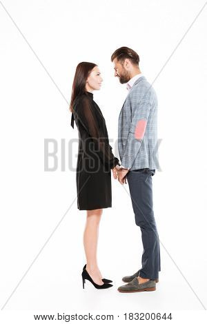 Picture of young happy loving couple standing isolated over white background. Looking aside.