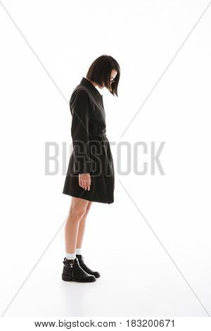 Image of concentrated young lady wearing sunglasses posing isolated over white background. Looking aside.