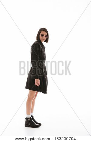 Picture of serious young lady wearing sunglasses posing isolated over white background. Looking at camera.