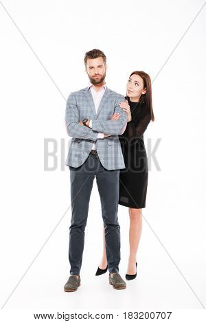 Image of young loving couple standing isolated over white background. Looking aside and camera.