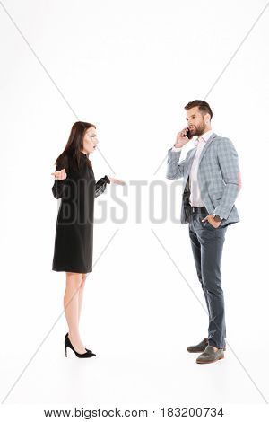 Angry woman looking at man talking by phone isolated over white background. Looking aside.