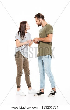 Image of angry young loving couple standing isolated over white background. Looking aside and holding phone.