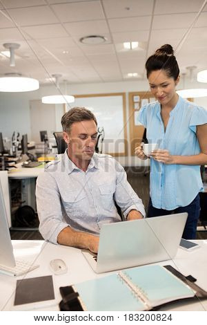 Businesswoman standing by male colleague working on laptop at desk in office