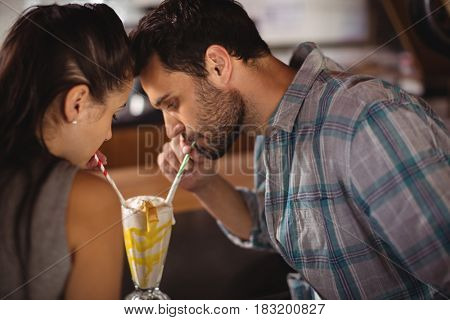 Close-up of couple having milkshake in restaurant