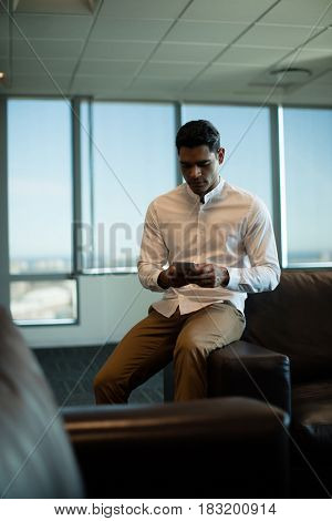 Young businessman using mobile phone while sitting on sofa at office