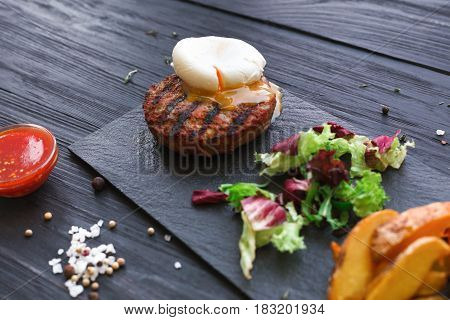 Grilled beef steak with poached egg and roasted potato wedges on black wood table background. Juicy meat with rosemary, lettuce and cutlery on stone board. restaurant food