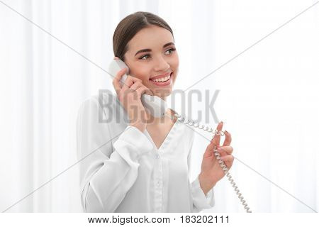 Beautiful young woman talking by telephone indoors