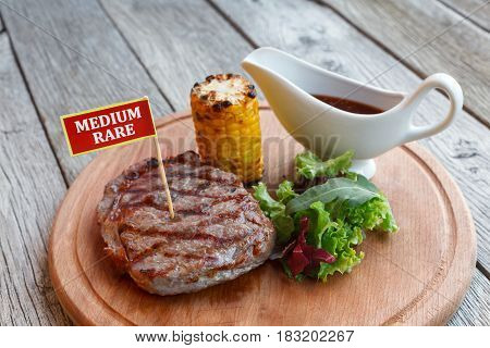 Grilled beef steak medium rare, barbecue closeup on dark rustic wood background. Meat restaurant food, delicious dish