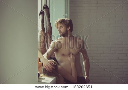 Muscular man or macho with fit naked torso biceps triceps. Pretty girl or sexy woman lying with legs up in black fishnet tights and shoes with high heels on white window sill poster