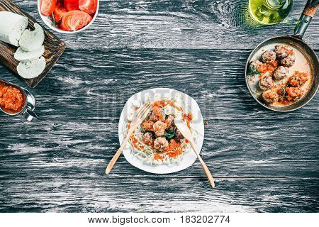 Plate of spaghetti with meatballs. Frying pan, fresh tomatoes, homemade cheese and spices on black and white wood background. Top view