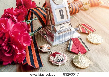VELIKY NOVGOROD,RUSSIA-CIRCA APRIL,2017. 9 May Victory Day still life - vintage metal desk calendar with 9 May date medals George ribbon red carnations bouquet - 9 May concept. Selective focus at the calendar