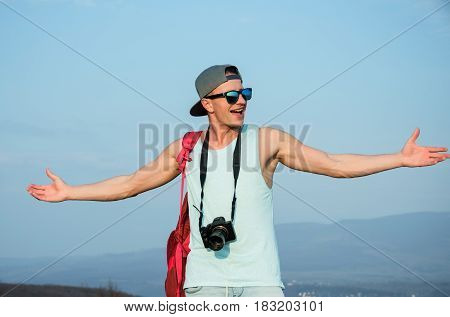Happy handsome man photographer or traveler in fashion sunglasses and cap posing with camera and red backpack on sunny summer day on blue sky. Photography and hobby
