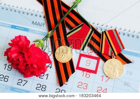 VELIKY NOVGOROD,RUSSIA-CIRCA APRIL,2017. 9 May - medals of Great patriotic war with red carnation and George ribbon lying on the calendar with framed 9 May date. 9 May concept