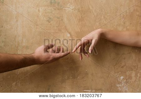 Male and female hands reaching to each other on abstract cement wall on beige background. Help and care