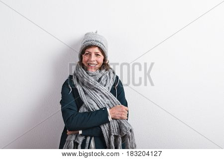 Beautiful senior woman in gray woolen hat and scarf, smiling. Studio shot against white wall.