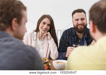 Happy couple have dinner with friends, home party. People have meals together, friendly conversation