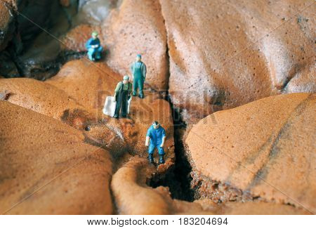 Miniature people: Villagers are exploring a pond on a cake of chocolate cake.
