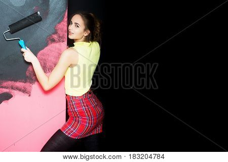 Pretty Girl Builder, Painter With Roller Painting Wall In Black