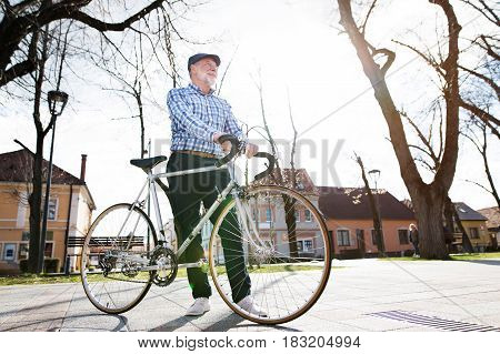 Handsome senior man in blue checked shirt with bicycle in town, looking up. Sunny spring day.