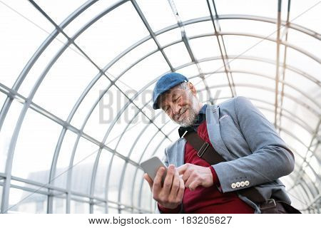 Handsome senior man in gray jacket holding smart phone, texting. Glass ceiling background.