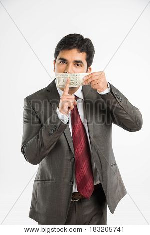 indian businessman holding indian currency note covering mouth or face and asking to keep silence or secret