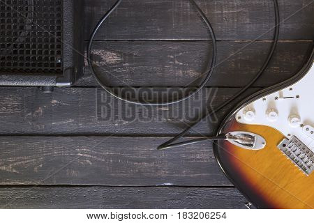 Electric Guitar And Black Amplifier Connected By Cable On Wooden Floor