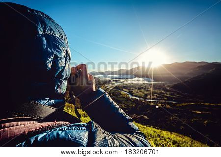 Photographer taking a picture of sunrise over the hills