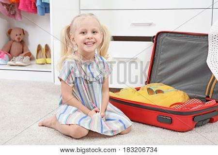 Cute small girl with suitcase in wardrobe