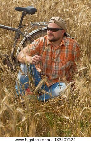 Matured traveller in cap and sunglasses having a rest at ripe wheat field with a bicycle on background