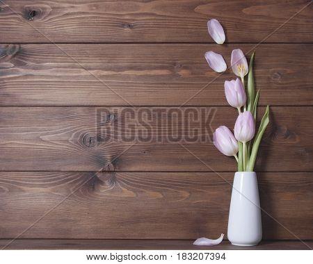 Wooden background witn pink tulip flowers on vese. Still life
