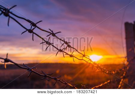 Fence with barbed wire on the background of the bright sunset and storm clouds