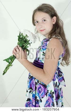 Cute teen girl with bouquet of flowers on white background