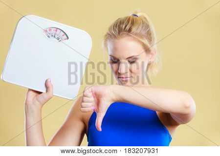 Frustrated sad blonde girl holding scales making thumb down gesture sign. Weight gain time for slimming weightloss diet.