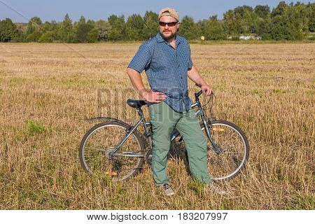 Matured man in cap and sunglasses standing with bicycle at the field