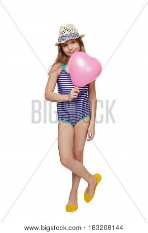 Full length child girl in swimsuit and summer hat with pink balloon heart shape, studio portrait