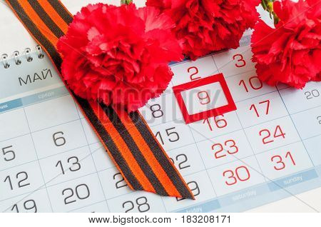 9 May - red carnation with George ribbon lying on the calendar with framed 9 May date. Festive 9 may postcard