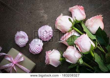 Pink rose present and pink dessert at dark stone table. Top view copy space.