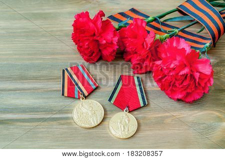 VELIKY NOVGOROD,RUSSIA-CIRCA APRIL,2017. 9 May composition - medals of Great patriotic war with red carnations and George ribbon lying on the wooden table. 9 may background
