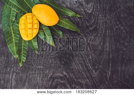 Mango And Mango Leaves On An Old Wooden Background