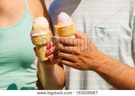 Diet food sweets summer pleasures concept. Man and woman hand holding two ice cream.