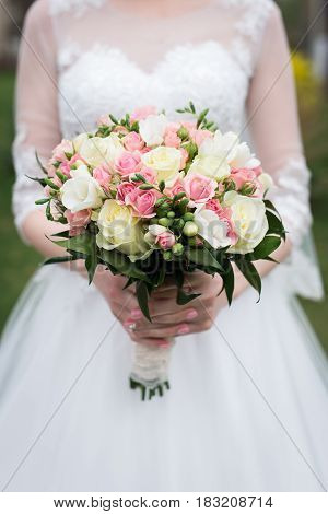 Bridal bouquet with white and pink roses. Wedding. The bride in white wedding dress holds a wedding bouquet with white and pink roses, greenery.