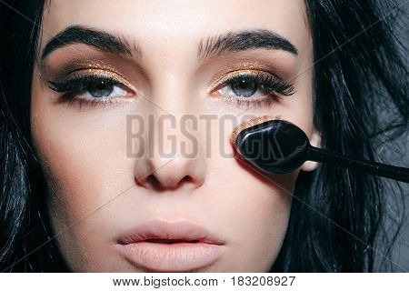 foundation make up brush near face of pretty woman or cute sexy girl with brunette hair has long eyelashes and fashionable eye makeup on adorable face. beauty and cosmetics